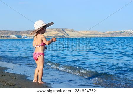 Cute Little Girl In A Big Hat  Is Playing The Spray Of Waves At Sea On A Sunny Day