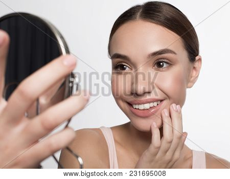I Like My Skin. Portrait Of Cheerful Girl Is Standing And Looking At Mirror With Admiration. She Is