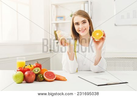 Dietitian With Bun And Fresh Orange. Woman Nutritionist Holding Fruit And Croissant Comparing Junk A