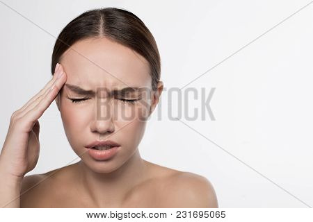 Awful Pain. Portrait Of Anguish Girl Is Standing With Closed Eyes And Touching Her Temple While Feel