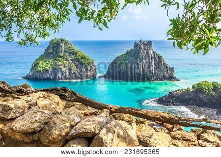 Fernando De Noronha, Brazil. View Of Morro Dos Dois Irmaos With Gains And Plants In The Foreground.