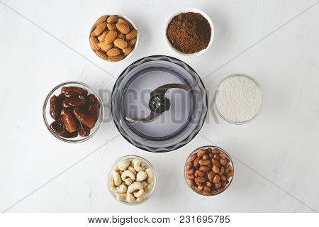 Ingredients For Energy Bites: Nuts, Dates, Cocoa Powder And Coconut Flakes With Food Processor On Wh