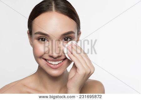 Relieving Skin. Portrait Of Attractive Young Woman Is Standing And Using Cotton Pad While Removing M