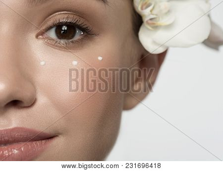 Healthy Skin Concept. Close Up Half Of Face Of Positive Attractive Young Woman With Orchid Is Lookin