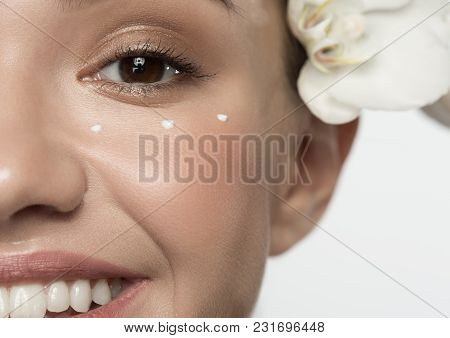 Skin Care Concept. Close Up Half Of Face Of Cheerful Girl With Drops Of Moisturizer Cream On Her Fac