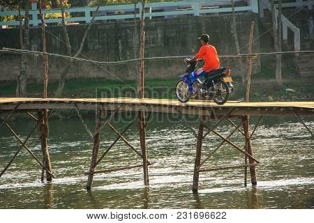 Local Man Riding Motorbike On The Bridge In Vang Vieng, Laos. Vang Vieng Is A Tourist-oriented Town