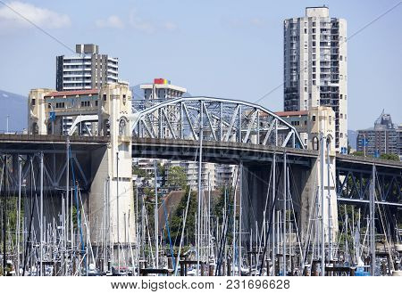 The View Through Yacht Masts Of Art Deco Style Burrard Street Bridge In Vancouver Downtown (british