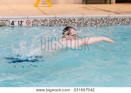 Horizontal Image Of A Caucasian Young Adult  Male  Wearing Goggles Swimming With Great Moyion In An