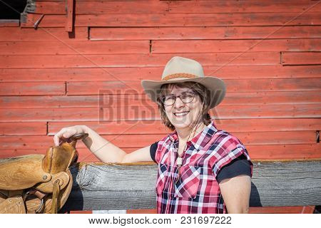 Horizontal Image Of The Upper Torso Of Caucasian Woman Wearing A Cowboy Hat And Checkered Shirt Lean