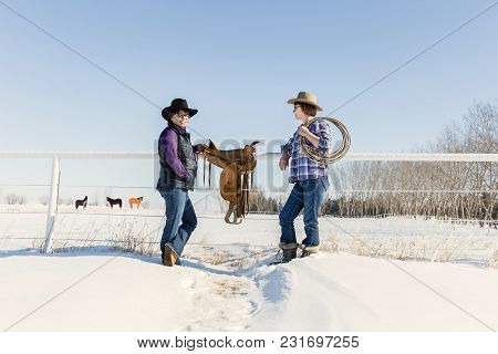 Horizontal Image Of Two Caucasian Cowgirls Standing Against A Fence With A Leather Saddle And Horses