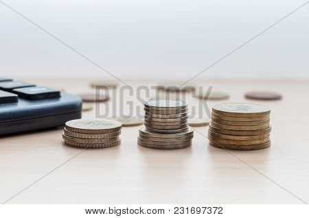 Three Stacks Of Coins And A Calculator Are On The Table