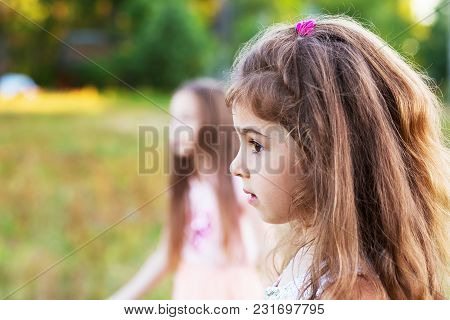 Beautiful Little Girl With Long Curly Hair, Looking Worried At Summer Day.  Place For Text