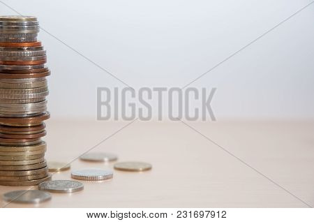 A Stack Of Coins Of Different Countries, Color, Dignity And Size On The Left At The Edge Of The Pict