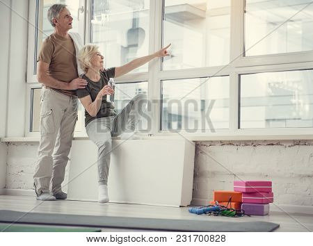 Low Angle Of Glad Old Woman And Her Husband Relaxing At Fitness Studio, Lady Is Pointing Out At Wind