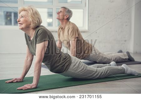 Pleased Mature Lady Lying On Carpet And Pushing Up On Outstretched Arms. Senior Man In Same Posture