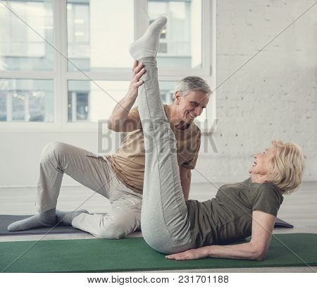 Cheerful Aging Woman Lying On Carpet With Raised Legs. Her Husband Sitting Beside Her. They Are Look