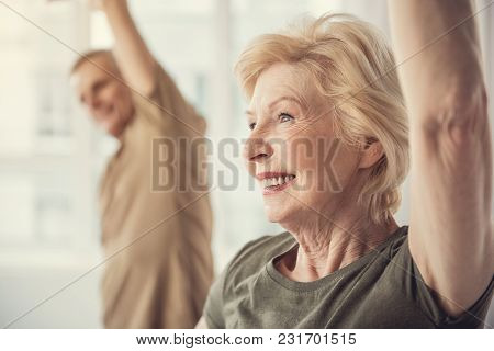 Contented Senior Female Standing With Raised Arm. Male On Background. Focus On Woman