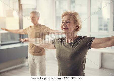 Waist Up Portrait Of Old Jolly Lady With Arms Straightened Out Aside. Male Pensioner In Same Posture