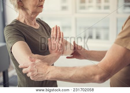 Peaceful Old Lady With Hands Clasped At Her Chest Standing In Front Of A Man Touching Her Elbows