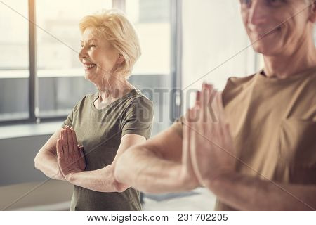 Delighted Senior Woman Standing With Hands Clasped At Her Chest And Smiling. Old Man In Same Posture