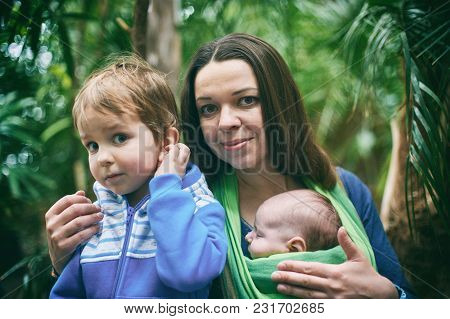 A Young Mother With A Baby In A Sling And Little Boy Is Walking In The Tropical Forest