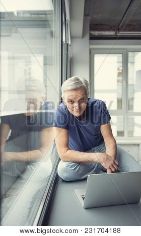 Portrait Of Tranquil Senior Man Resting Near Window With Laptop. He Is Looking At Camera