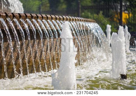 Fountain In City Park On Hot Summer Day, Beautiful Bright Streams Of Sparkling Water, Drops And Spla