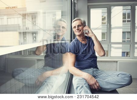 Portrait Of Happy Pensioner Resting On Windowsill And Communication By Cellphone. Copy Space In Left