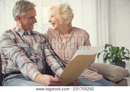 Mature Husband And Wife Sitting In Embrace With Papers In Hand. Their Expressions Are Happy