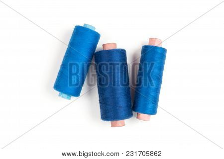 Three Blue Sewing Threads On A White Background