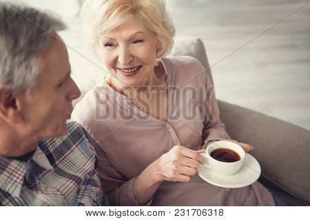 Smiling Granny Holding Cup Of Tea While Resting And Talking With Senior Man Indoors