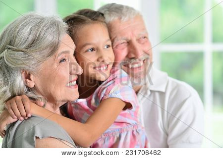 Grandparents With Her Granddaughter Posing At Home