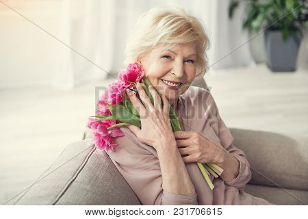 Portrait Of Old Woman Relaxing On Cozy Sofa With Bunch Of Flowers In Hug. She Is Looking At Camera W
