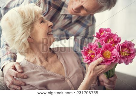 Cheerful Elderly Woman Resting On Couch With Beautiful Flowers In Hands. Husband Hugging Her From Be