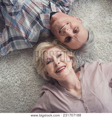 Top View Portrait Of Mature Man And Woman Resting On The Floor With Their Heads Close To Each Other.
