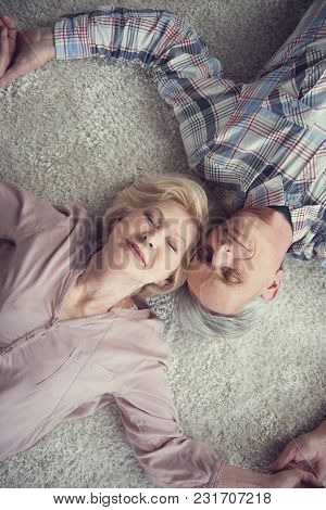 Top View Portrait Of Calm Senior Couple Resting On Warm Carpet With Their Heads Together And Eyes Cl