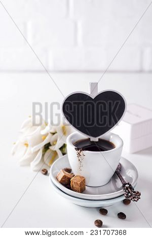 Cup Of Black Coffee On A Saucer With Brown Sugar And Coffee Beans On A White Background With A Black