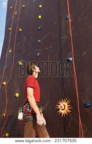 Young Climber Ready To Conquer Vertical Training Artificial Climbing Wall With Belay Harness And Equ