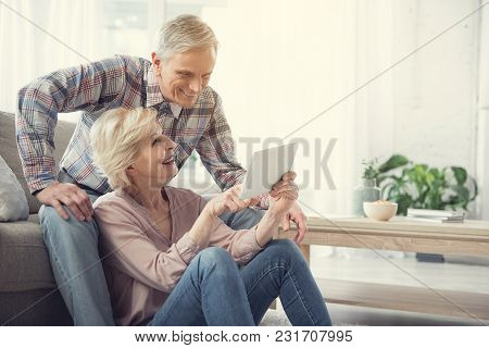 Happy Old Woman Sitting On The Floor And Pointing At Tablet To Her Husband. Glad Man Is Resting On C