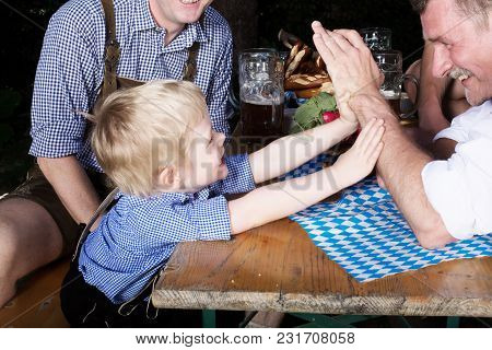Portrait Of Young Bavarian Boy With Father At Beergarden