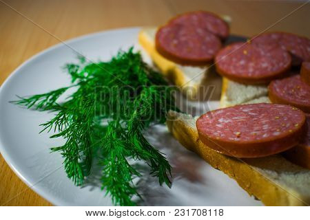 Appetizing Homemade Sandwiches With Meat Sausage On A White And Round Plate, Decorated With Dill - F