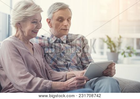 Old Man And Woman Resting On Sofa At Home And Looking At Modern Technology In Their Hands With Inter