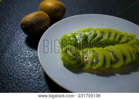 Green Ripe Tropical Kiwi On A White Plate On A Dark Black Background, Sliced, Tasty And Sour. Lobule