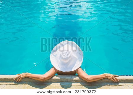 Young Woman With Tanned Skin In White Hat Resting In A Pool, Top View