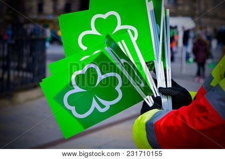 Man Holding Green Flags With Shamrock Symbol For St Patricks Day Celebration.  March, 17, 2018, Belf