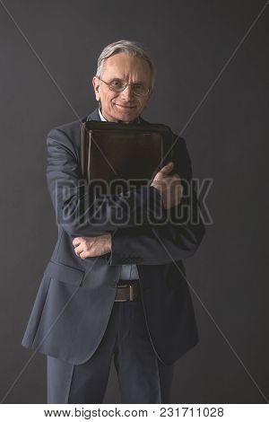 Portrait Of Smiling Senior Male Embracing Bag While Looking At Camera. Happy Entrepreneur Concept