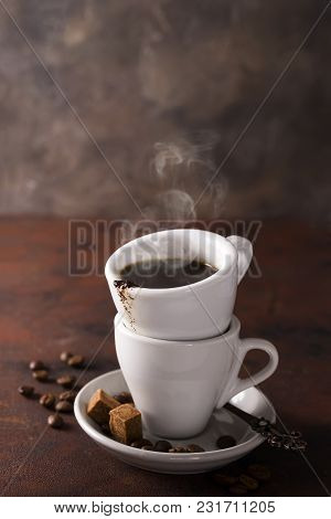 Cup Of Black Coffee On A Saucer With Brown Sugar And Coffee Beans On A Stone Brown Background With C