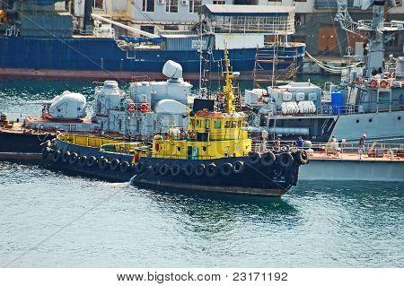 Tugboat at military ship at harbor