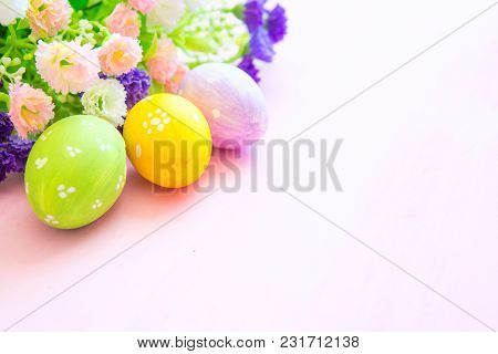 Easter Eggs In Pastel Color With Flowers On Wooden Pale Pink Background.