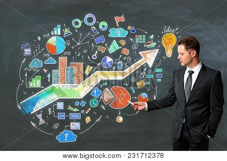 Presentation And Growth Concept. Portrait Of Handsome European Businessman Standing On Chalkboard Wa